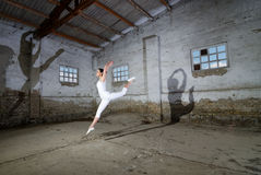 Beautiful ballerina in white dancing jumping in abandoned building Stock Image