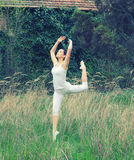 Beautiful ballerina in white dancing in nature high grass on bea Royalty Free Stock Image