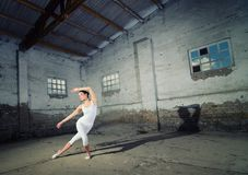 Beautiful ballerina in white sports clothes dancing in abandoned Stock Photos