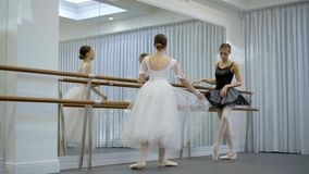 Beautiful ballerinas are practiced near barre in ballet studio. Young ladies stand in front of mirror and perform classical dance techniques, holding on to bar stock video footage
