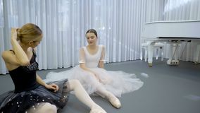 Beautiful ballerinas are talking in ballet studio indoors. Young dancers sitting on floor and speaking with friendly smiles, one of them touching hairstyle stock footage