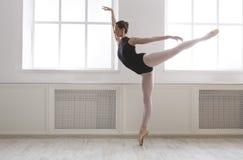 Beautiful ballerine stands in arabesque ballet position. Classical Ballet dancer side view. Beautiful graceful ballerine in black practice arabesque ballet Royalty Free Stock Image