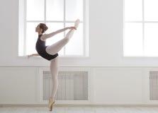 Beautiful ballerine stands in arabesque ballet position. Classical Ballet dancer side view. Beautiful graceful ballerine in black practice arabesque ballet Stock Photography