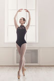 Beautiful ballerine stands in fifth ballet position Royalty Free Stock Photography