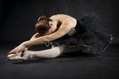Beautiful ballet dancer. Beautiful expressive ballerina in the role of a black swan, wearing black tutu and pointe shoes on black background Royalty Free Stock Photo