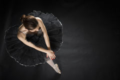 Beautiful ballet dancer. Beautiful expressive ballerina in the role of a black swan, wearing black tutu and pointe shoes on black background Royalty Free Stock Photography