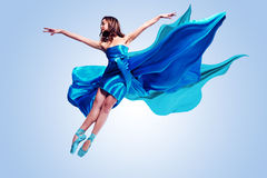 Ballet Dancer. Beautiful ballet dancer with flowing blue fabric dancing with grace in studio Royalty Free Stock Photo