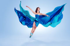 Ballet Dancer. Beautiful ballet dancer with flowing blue fabric dancing with grace in studio Stock Images