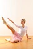 Beautiful ballet dancer lifting arm towards leg Royalty Free Stock Images