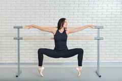 Beautiful ballet dancer practicing near barre at ballet studio, Ballerina full length portrait. Royalty Free Stock Photo