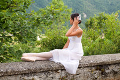 Beautiful ballet dancer in romantic dress sitting in the nature. On stone wall with pointe shoes royalty free stock photos