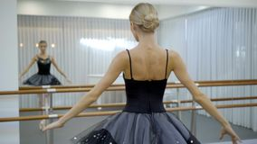 Beautiful ballet dancer is turning with body in ballet school indoors. Young female is practicing ballet movements in modern studio. Attractive blonde in stock footage