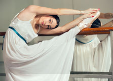 Beautiful ballet dancer in white tutu posing on one leg next to handle bar. Royalty Free Stock Images