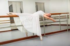 Beautiful ballet dancer in white tutu posing on one leg next to handle bar. Stock Photography