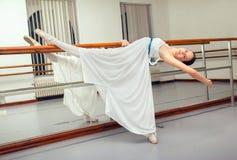 Beautiful ballet dancer in white tutu posing on one leg next to handle bar. Royalty Free Stock Photos