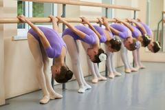 Beautiful ballet dancers training at ballet barre. Group of young ballerinas stretching in ballet hall. Dance skills and education concept Royalty Free Stock Photos