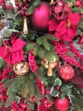 Beautiful balls, red flowers and other brightly colored ornaments on a Christmas tree. Stock Photos