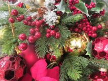 Beautiful balls, red flowers and other brightly colored ornaments on a Christmas tree. Royalty Free Stock Photos