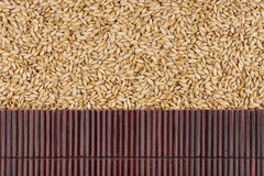 Beautiful bamboo mat on barley grains as agricultural background. Stock Photography