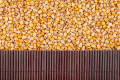 Beautiful bamboo mat on corn grains as agricultural background. Stock Image