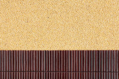 Beautiful bamboo mat on millet grains as agricultural background. Royalty Free Stock Image