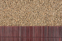 Beautiful bamboo mat on rye grains as agricultural background. Royalty Free Stock Photos