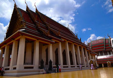 Beautiful Bangkok Temple. Interior courtyard of a Buddhist Temple in Bangkok, Thailand. Reds and Golds set against a cobalt blue sky Royalty Free Stock Images