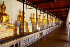 Beautiful Bangkok Temple. Beautiful interior to a temple in Bangkok Golden Buddas line to who length of the walkway which opens onto a courtyard Royalty Free Stock Photos
