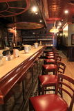 Beautiful bar inside on of the city's finest restaurants,Lillian's,Saratoga Springs,New York,2015. Beautiful length of bar and stools inside one of the city's Royalty Free Stock Photo