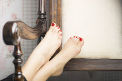 Beautiful barefoot with gel red pedicure on wooden chair. Foot with red gel pedicure on white towel Royalty Free Stock Photography