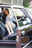 Beautiful barefoot woman dressed in a shirt and shorts sits in a car Stock Image