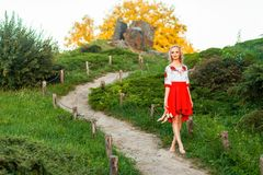 Beautiful barefoot woman in stylish red white dress holding shoes in hand and walking on path at hill. standing on road village. And looking away with smile royalty free stock photos