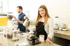 Beautiful barista brewing some coffee. Portrait of a cute young female barista brewing a few cups of coffee for some customers at a cafe Royalty Free Stock Photo