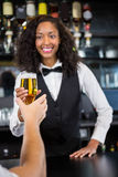 Beautiful barmaid serving beer to man Stock Images