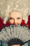Beautiful Baroque Woman Portrait with Wig and Fan. Baroque style portrait of a young beautiful woman behind a hand fan Royalty Free Stock Photos
