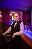 Beautiful bartender leaning at bar counter Royalty Free Stock Photos