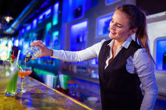 Beautiful bartender pouring drink in glass Stock Photos