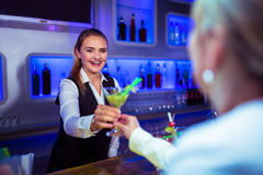 Beautiful bartender serving cocktail to woman Royalty Free Stock Photo