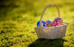 Beautiful basket with traditional painted Easter eggs in the garden Stock Photo