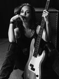 Beautiful bass player sitting with her guitar. Photo of a beautiful young bass player sitting with her guitar against an amplifier Stock Images