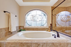 Beautiful bath tub in luxury bathroom. Beautiful bath tub with tile trim in soft ivory and light brown colors Royalty Free Stock Images