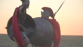 A beautiful battle of two legionaries in armor with shields and swords in the field against the backdrop of dawn. Two powerful Roman warriors are fighting in the stock footage