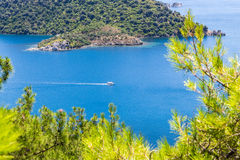 Beautiful bay in the Aegean Sea with blue water and pine trees in the mountains. View of the blue sea bay and mountains with pine trees against the sky royalty free stock photography