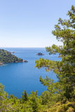 Beautiful bay in the Aegean Sea with blue water and pine trees in the mountains. View of the blue sea bay and mountains with pine trees against the sky royalty free stock images