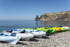 Kayaks lying on a pebble beach on sunny summer day. Stock Image