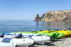 Colorful kayaks lay on the beautiful seashore. Royalty Free Stock Photo