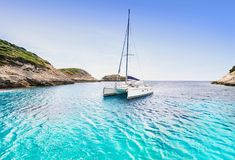 Beautiful bay with sailing boat catamaran, Corsica island, France royalty free stock images