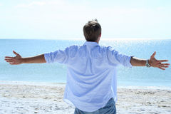 Beautiful Beach. Man lifting his arms out to sides looking at ocean Royalty Free Stock Image