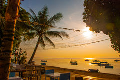 Beautiful beach with a cafe in Sanur with local traditional boats Palm trees on the island of Bali at dawn. Indonesia Stock Photos