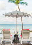 Beautiful beach chairs with umbrella around outdoor swimming poo Stock Photography